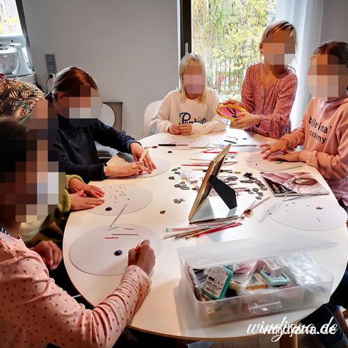 Kinder am Tisch modellieren gemeinsam Schmuck